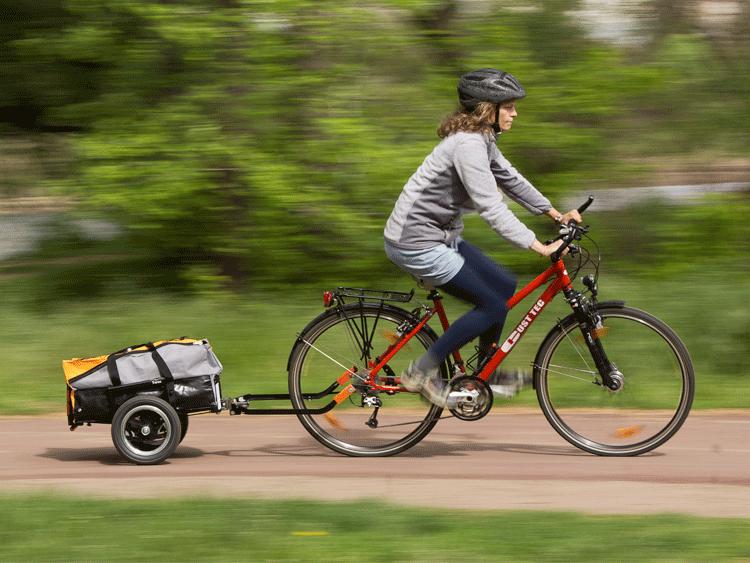 Foto zeigt eine Frau auf einem Fahrrad mit ausgeklapptem Trenux Fahrradanhänger