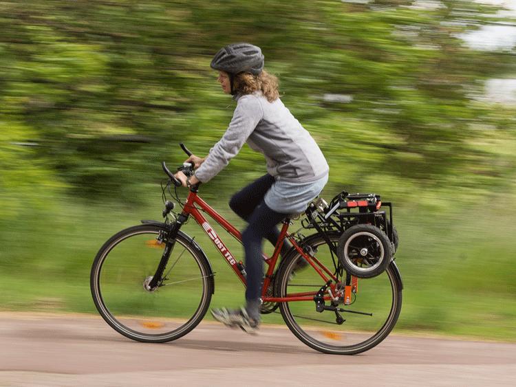 Foto zeigt eine Frau auf einem Fahrrad mit eingeklapptem Trenux Fahrradanhänger